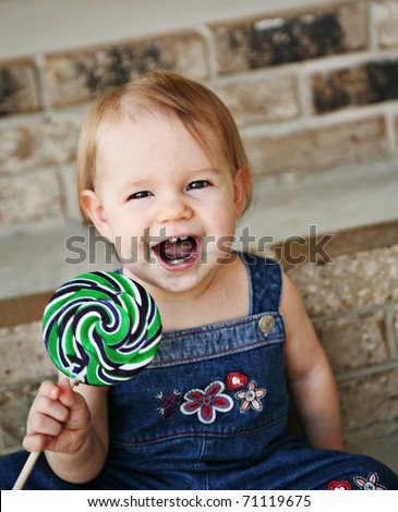 Toddler girl eating a messy lollipop sucker - stock photo