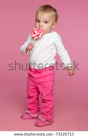 Toddler girl eating lollipop candy - stock photo