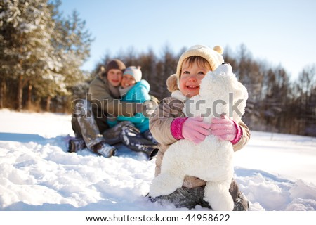 Toddler girl embracing bear toy and her parents looking at her behind - stock photo