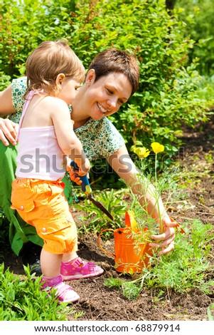 Toddler girl enjoying time in the garden - stock photo