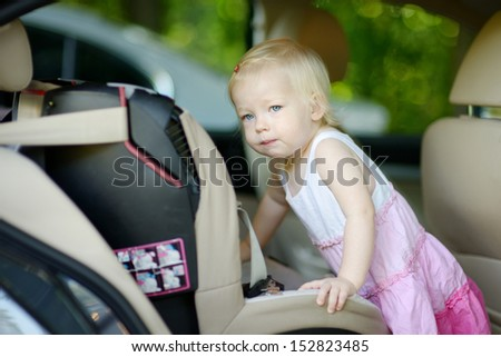 Toddler girl getting into her car seat - stock photo