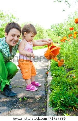 Toddler girl helping mom in the garden - stock photo