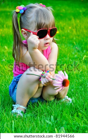 Toddler girl in sunglasses holding flower - stock photo