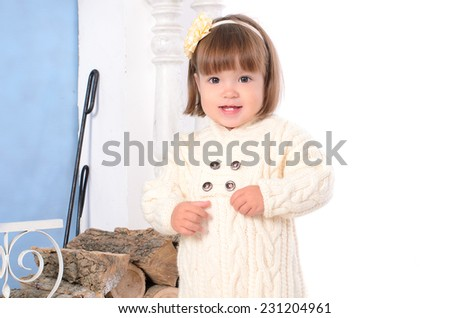 toddler girl in white knitted overalls near woodpile indoors