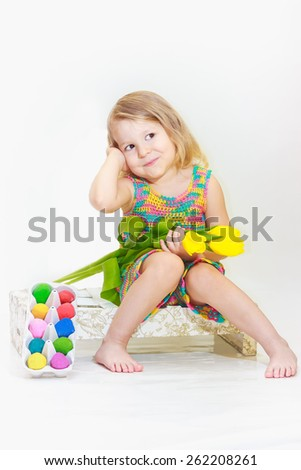 Toddler girl is holding tulips with Easter eggs  - stock photo
