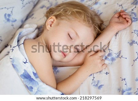 toddler girl is sleeping covered with a blanket - stock photo