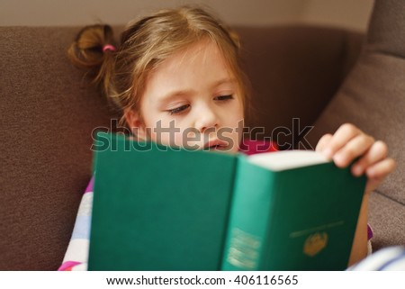 toddler girl is trying to read a book