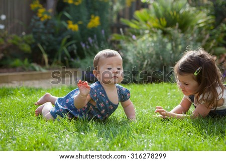 Toddler girl laying on a grass with her baby sister, selective focus