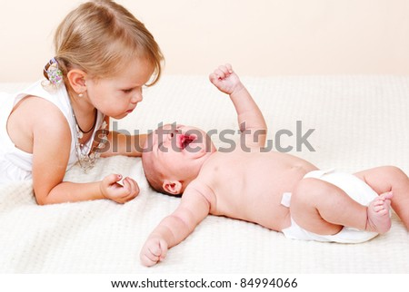 Toddler girl looking at her newborn brother crying - stock photo