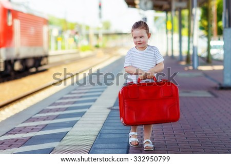 Toddler girl of 3 years walking with big red suitcase on a railway station. Kid waiting for train and happy about a journey. People, travel, lifestyle concept - stock photo