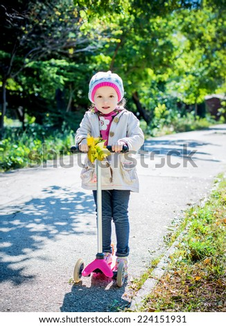 toddler girl on a scooter in a park in autumn day - stock photo