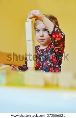 toddler girl playing blocks at the table - stock photo