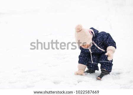 Toddler girl playing in the snow, wearing wool gloves and hat and a blue winter suit