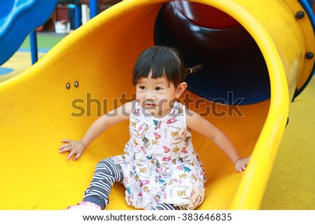 toddler girl playing on the slider - stock photo