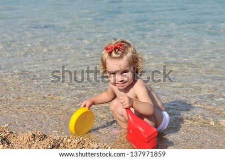 toddler girl playing toys in sea water - stock photo