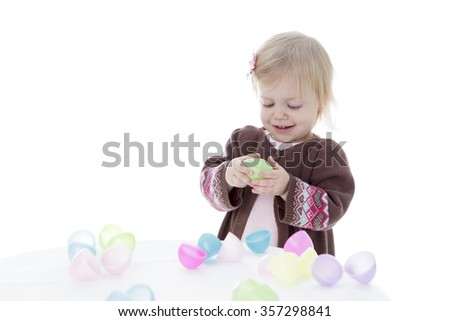 toddler girl playing with colored building blocks, holding in hands, isolated on white background
