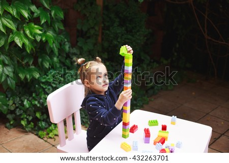 Toddler girl playing with constructor, building a tower in a green garden on wooden table. - stock photo