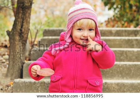 toddler girl pointing her nose and holding leaf - stock photo
