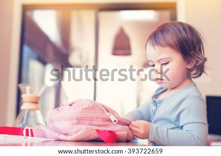 Toddler girl preparing her backpack in her house - stock photo