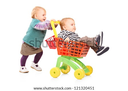 Toddler girl pushing her twin brother in a toy cart isolated on white background - stock photo