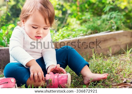 Toddler girl putting on her sneakers outside - stock photo