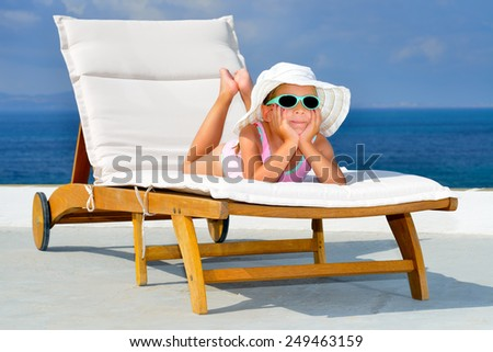 Toddler girl relaxing on sunbed - stock photo