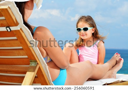Toddler girl relaxing on sunbed with her mother - stock photo