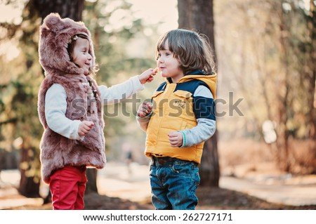toddler girl sharing cookie with her friend on the walk - stock photo