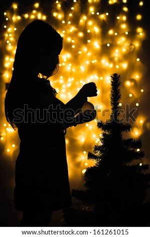 Toddler girl silhouette dresses up Christmas tree - stock photo