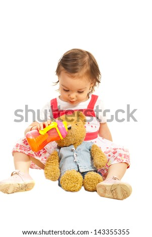 Toddler girl sitting and giving juice to her fluffy bear toy isolated on white background - stock photo