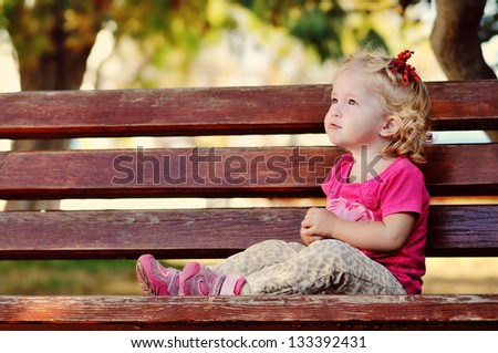 toddler girl sitting on  the bench - stock photo