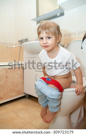 Toddler girl sitting on   toilet bowl