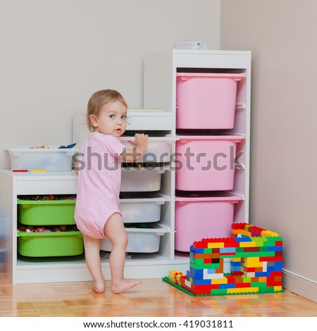 Toddler girl standing near toys sorting system. Toys arrangement in room: safety, easy and comfortable.  - stock photo