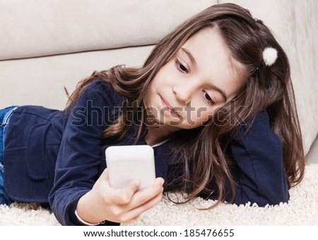 Toddler girl typing sms text message and lying on the floor - stock photo
