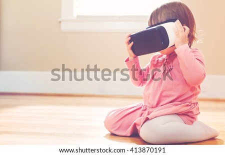 Toddler girl using a new virtual reality headset - stock photo