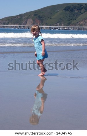 toddler girl walking on the beach, nice reflection on the wet sand.