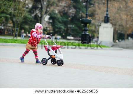 toddler girl walking with a toy stroller