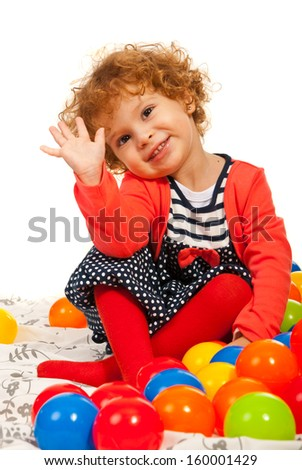 Toddler girl waving and sitting down with colorful balls - stock photo