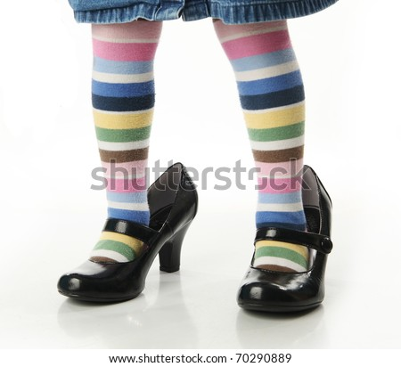 Toddler girl wearing bright colored striped tights trying on mother's high heel shoes