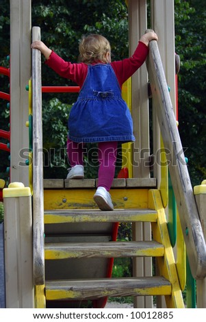 Toddler girl wearing jeans dress on playground back view - stock photo