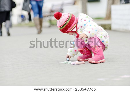toddler girl with chalk is drawing outdoors - stock photo