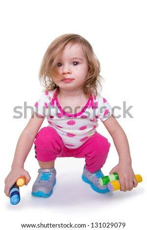 Toddler girl with colorful crayons in her hands getting ready for activity time, looking at camera. Isolated on white.