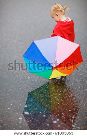 Toddler girl with colorful umbrella, beautiful reflection on wet ground - stock photo