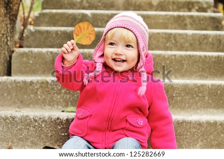 toddler  girl  with leaf on the stairs - stock photo
