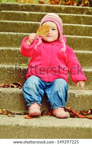 toddler girl with leaf sitting on the stairs - stock photo