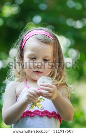 Toddler girl with white Taraxacum officinale or common dandelion seeds in arm - stock photo