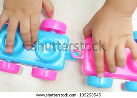 Toddler hands hooking up two train coaches together - stock photo