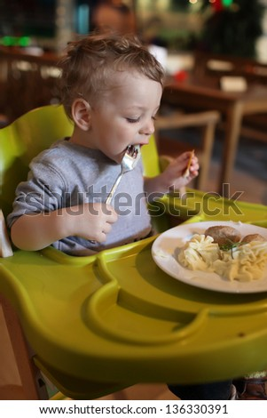 Toddler has a lunch in a high chair at a restaurant - stock photo