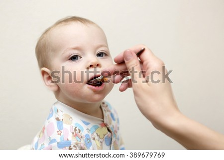 Toddler has dinner from the mother's hand