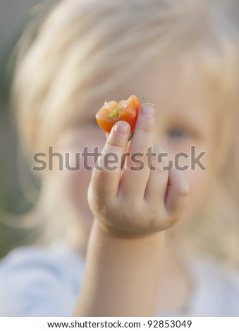 Toddler holding a half eaten cherry tomato towards the camera. Hand and tomato in focus, toddler out of focus.